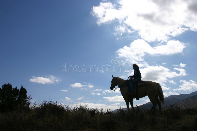 Evening ride. Person on horse in evening on hill with clouds stock photo