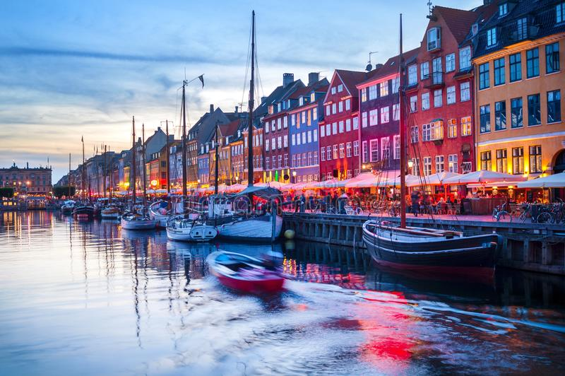 People Nyhavn harbor embankment, Sopenhagen. Evening scene with boats moored by illuminated Nyhavn harbor embankment, Copenhagen, Denmark royalty free stock photo