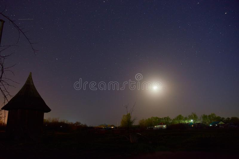 Night sky full of stars and sunrise. Purple dark sky with many stars above field of trees, house and moon royalty free stock photo