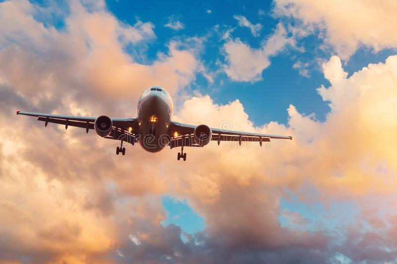 Evening sky with broken beautiful clouds of warm colors and airplane approaching the landing airport royalty free stock photos