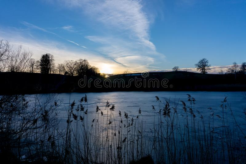 Evening sky over a frozen pond in Germany stock photography