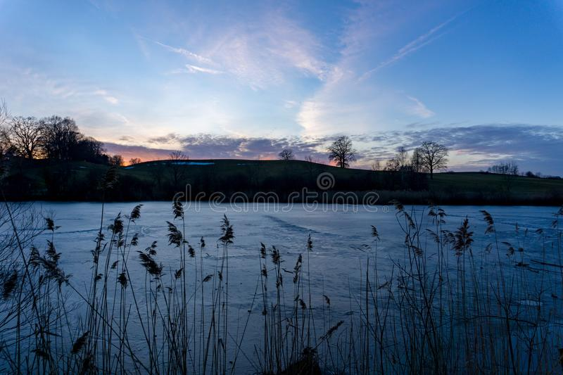 Evening sky over a frozen pond in Germany royalty free stock image