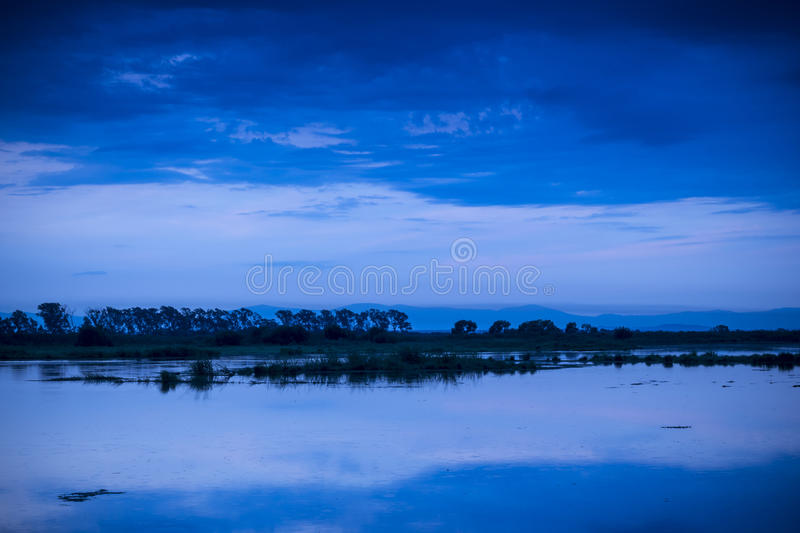 Evening sky over water. Beautiful evening sky and reflection clouds in water royalty free stock photo