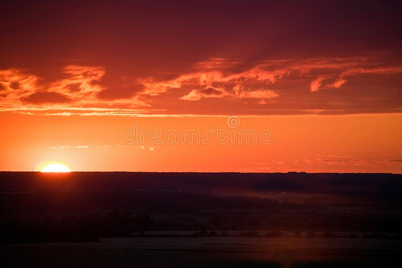 Evening sky and sun shine through the field. Sunset on the field stock image