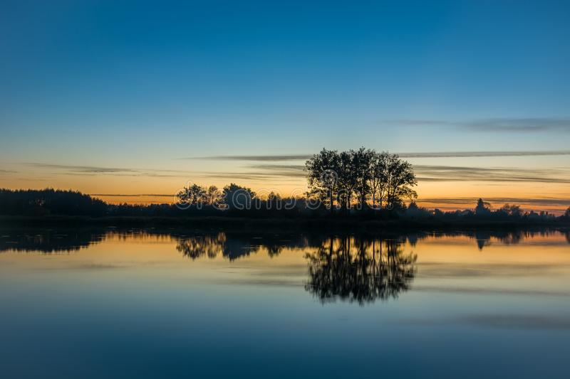 Evening sky and trees reflecting in the water stock photos