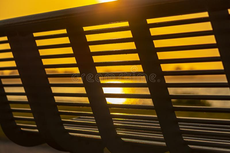 The evening sun shines through the bars of a bench along lake `Zoetermeerse plas`, Netherlands.  stock photo