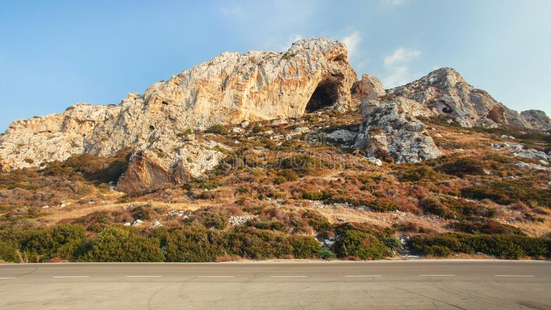Evening sun shines on typical landscape at Karpass region of Northern Cyprus, small rocky formations by asphalt road stock image