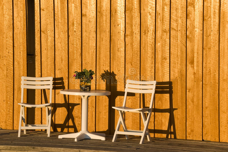 Evening sun on terace. Two white wooden chairs and a table in a sunny evening royalty free stock image