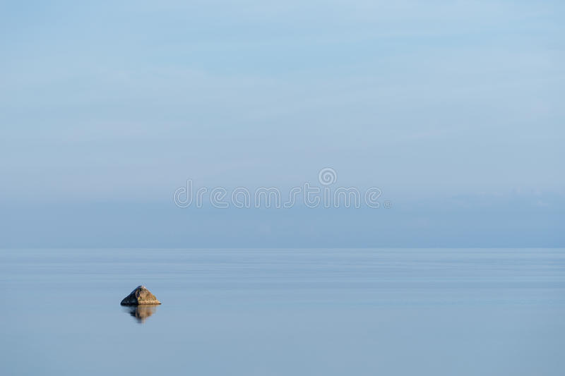 Evening sunlight on the coast, blue sky reflection on the water. Beach in summer. Seaside natural environment background. Shore in Osmussaar Island, Nature stock photos