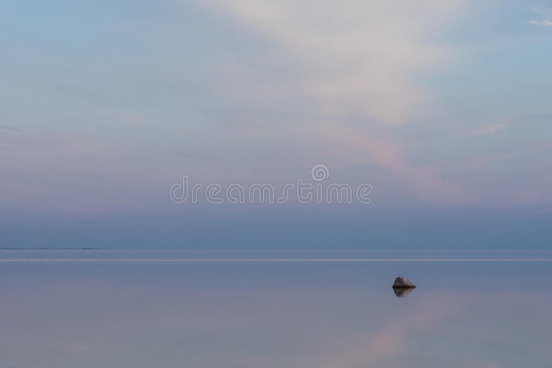 Evening sunlight on coast, pink clouds, blue sky reflection on water. Beach in summer. Seaside natural environment. Shore in Osmussaar Island, Nature Reserve royalty free stock photography