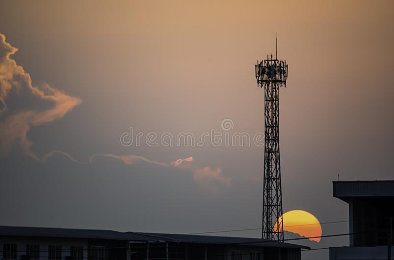 Evening sunset light is orange after the telephone receiver antenna.  stock image