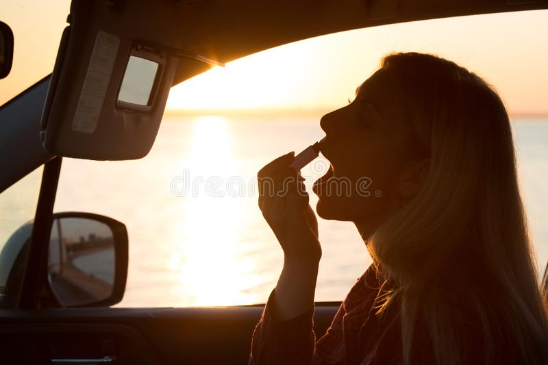 Beautiful woman paints her lips in the car .The evening sunset on the promenade royalty free stock image