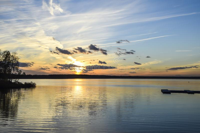 Evening sunset on the river sea bright light reflection water cl. Evening sunset on river sea bright light reflection water clouds sky royalty free stock images