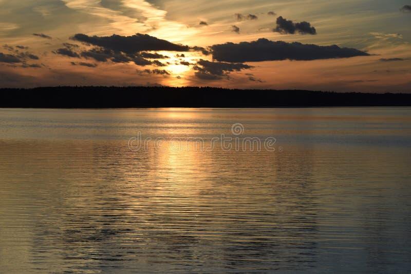 Evening sunset on the river sea bright light reflection water cl. Evening sunset on river sea bright light reflection water clouds sky royalty free stock photo