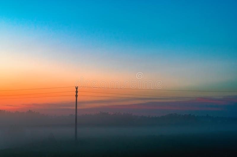 Evening thick fog over field and forest. Landscape of the evening sky with orange and blue sky and fog. Telegraph pole in the fog. stock images