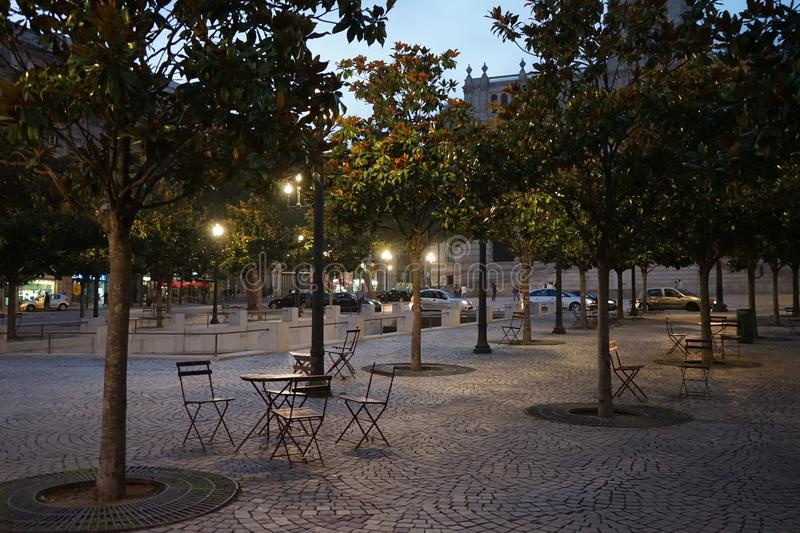 Evening time in Lisbon. Empty cobbled street, four chairs and one table, outdoor furniture, street life evening time in Lisbon stock image