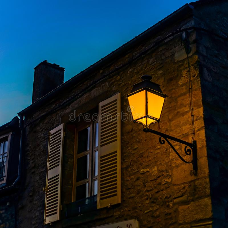 Evening time in old french city Vezelay. Light of old-styled street lantern. France royalty free stock photo