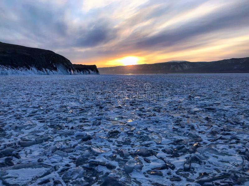 Evening view. Cracks on the surface of the blue ice. Frozen lake Baikal in winter mountains. It is snowing. The hills of pines. Ca stock images