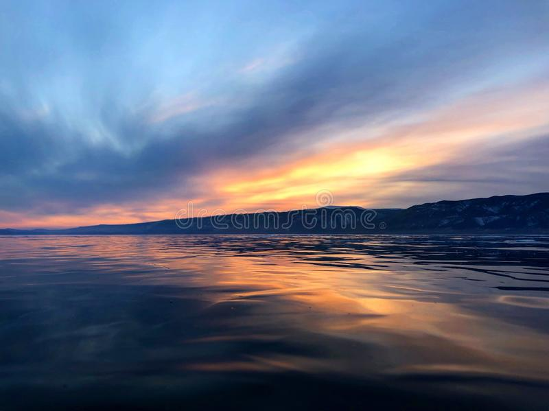 Evening view. Cracks on the surface of the blue ice. Frozen lake Baikal in winter mountains. It is snowing. The hills of pines. Ca royalty free stock image