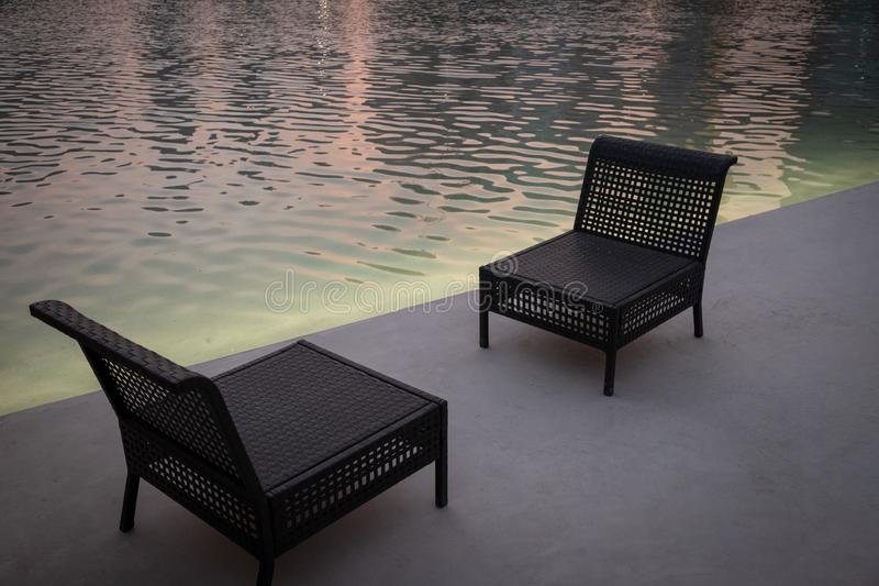 Evening view of Empty chairs near water pool royalty free stock image