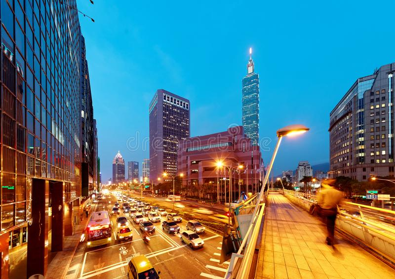 Evening view of a pedestrian footbridge over a busy street corner in Taipei City with Taipei 101 Tower & World Trade Center royalty free stock images
