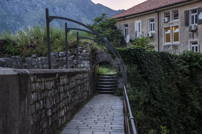 Evening view of the village, ladder, of the stone wall twined a rod and fence. Against the background of high mountains stock image