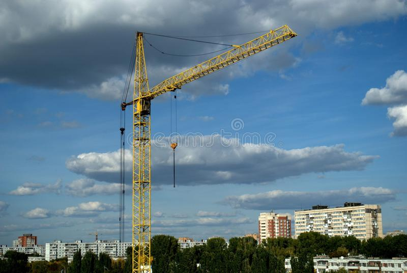 Evening view of a yellow tower crane on the background of the autumn panorama of the city and the blue sky with clouds. stock image