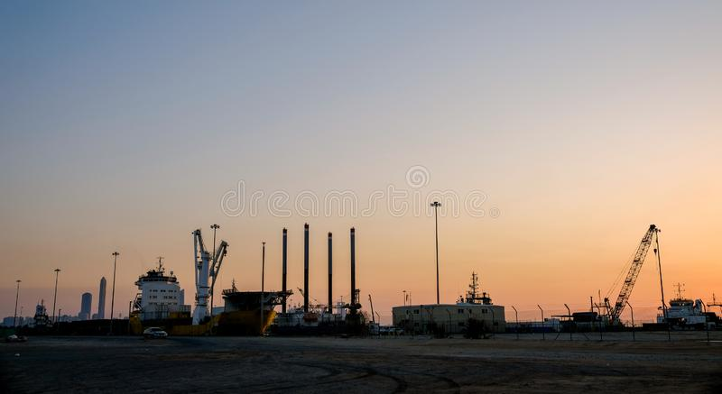 Evening view of Zayed Port with docked ships and oil rigs stock photo