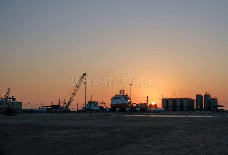 Evening view of Zayed Port with docked ships and oil rigs royalty free stock images