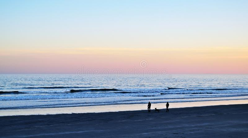 Evening walk on the beach stock photography