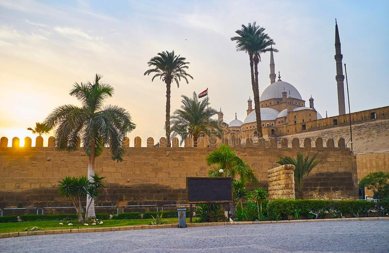 The evening walk at the Saladin Citadel with a view on sunset sky and the towering Alabaster Muhammad Ali Mosque behind the tall. Palm trees, Cairo, Egypt royalty free stock photo