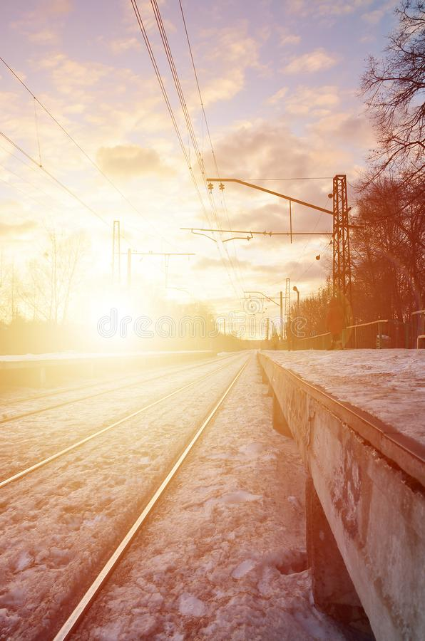 Evening winter landscape with the railway station. Snow-covered railway platform under the sun light at sunset. A place where peo. Ple waiting for a train royalty free stock photo