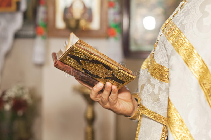 Evensong. Priest holding an open Bible and praying stock photos
