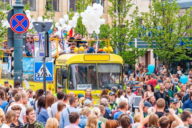 Evento del gay pride nell'azione Folla del bus senza coperchio giallo circostante degli osservatori decorato con i palloni bianch immagini stock