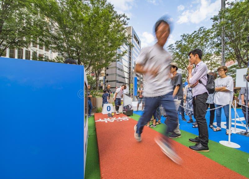Evento para os Jogos Olímpicos de Tóquio em 2020 Passers-by poderia testar 0m a correr disciplinas desportivas para redescobrir o imagem de stock