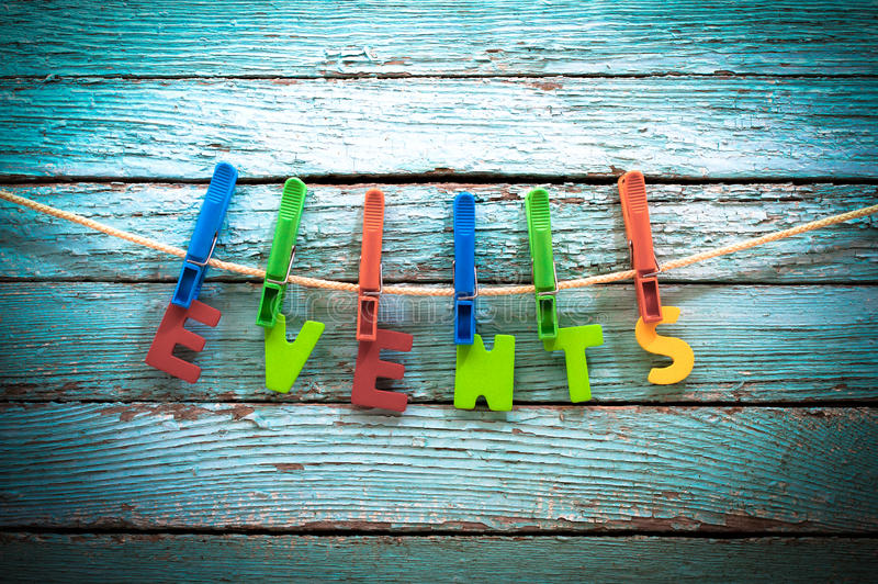 Events. Word events fasten clothespins on a rope behind a wooden background stock photo