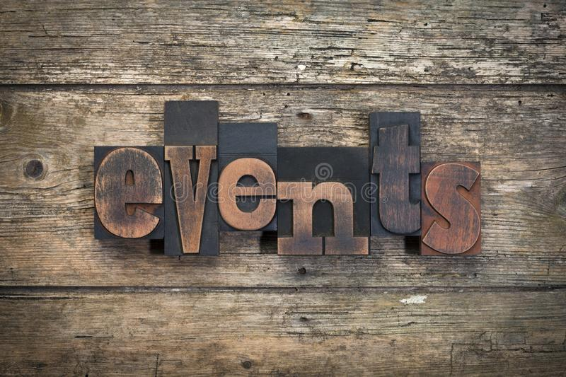 Events, word written with vintage letterpress printing block. Word events, written with vintage letterpress printing blocks on rustic wood background royalty free stock image