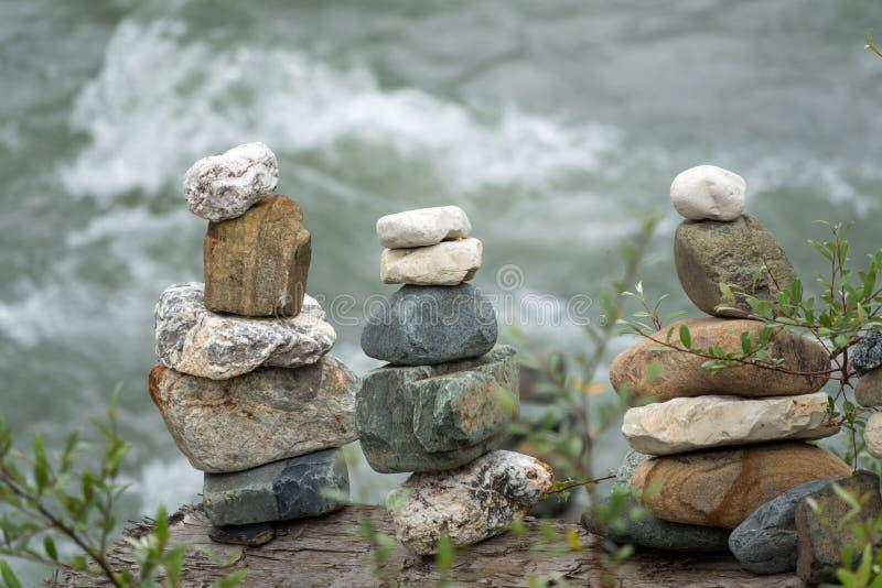 In evenwicht brengende stenen in evenwicht tegen de achtergrond van een bergrivier stock afbeeldingen