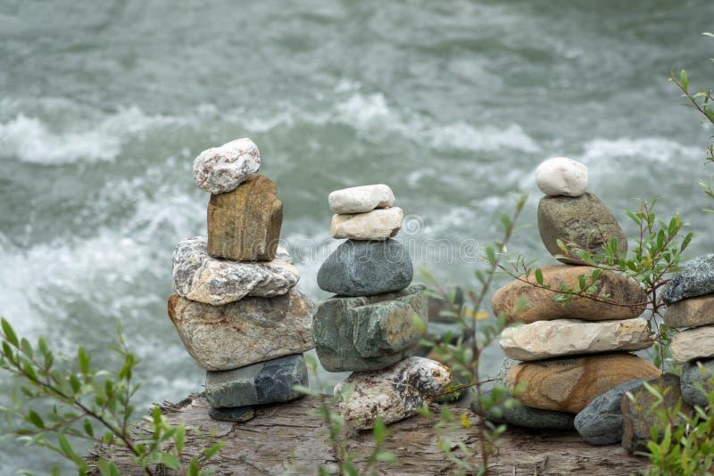 In evenwicht brengende stenen in evenwicht tegen de achtergrond van een bergrivier stock foto