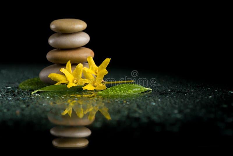 In evenwicht brengende zen stenen op zwarte met gele bloem royalty-vrije stock foto