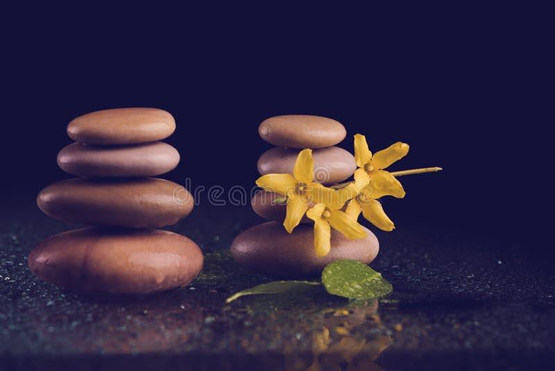 In evenwicht brengende zen stenen op zwarte met gele bloem royalty-vrije stock afbeelding