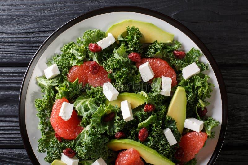 Evenwichtige salade van bladkool, avocado, grapefruit, kaas en droog Amerikaanse veenbessenclose-up op een plaat horizontale hoog royalty-vrije stock afbeeldingen