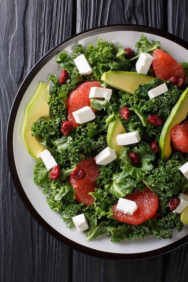 Evenwichtige salade van bladkool, avocado, grapefruit, kaas en droog Amerikaanse veenbessenclose-up op een plaat Verticale hoogst stock fotografie