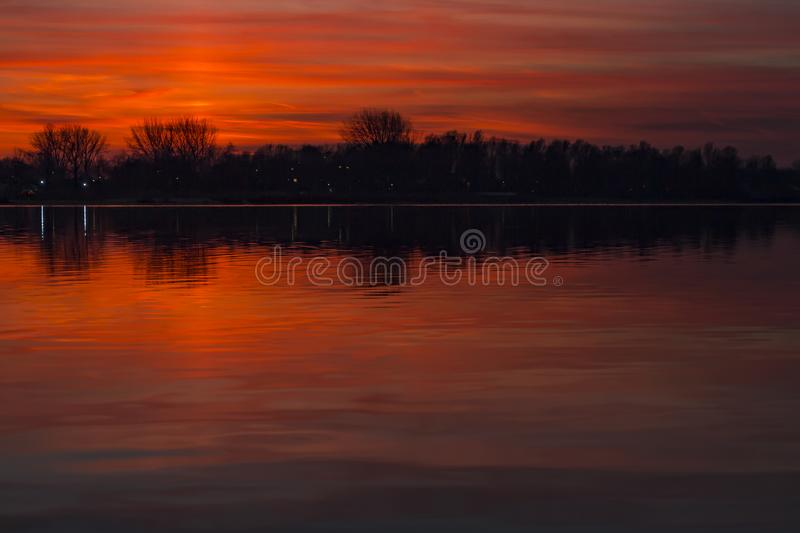 The ever changing pearly sky is beautifully reflected in the water of the Lake Zoetermeerse plas, Netherlands. The ever changing pearly sky is beautifully stock image