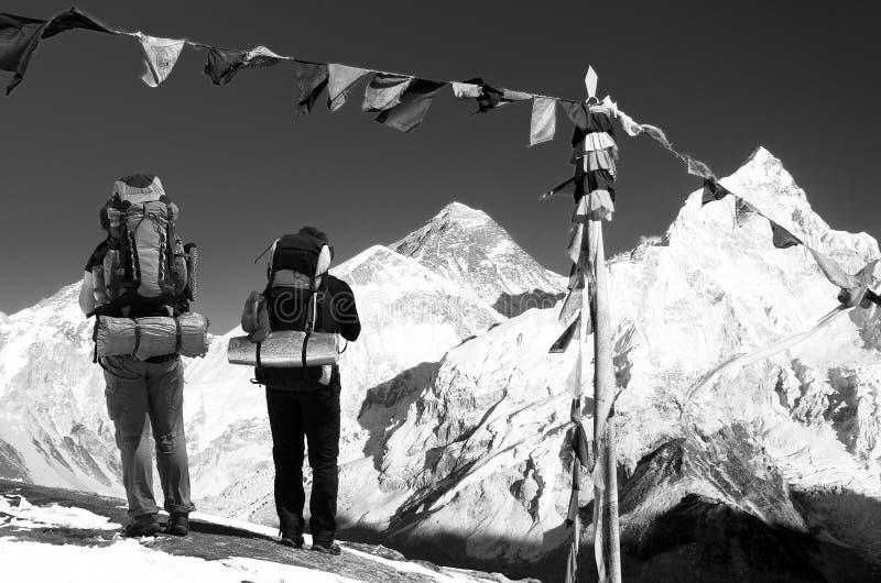 Everest med två turister och buddistiska bönflaggor royaltyfria bilder
