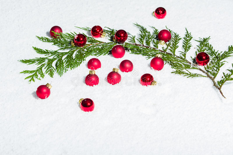 Evergreen bough with red ornaments. Evergreen bough in the snow with red Christmas ornaments stock photo