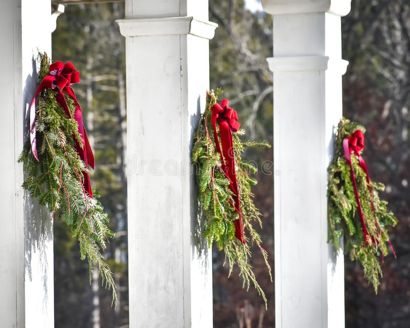 Evergreen Christmas Branches Hanging on White Pillars royalty free stock photo