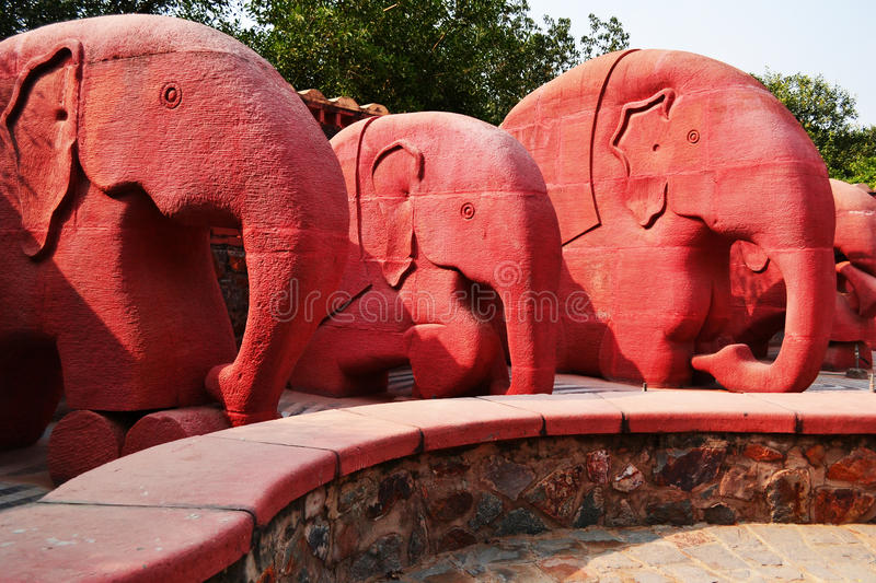 Every block of stone has a sculpture inside and its the work of sculpture to discover it -Michelangelo. Stone elephant fountain just after entering the Garden of royalty free stock images