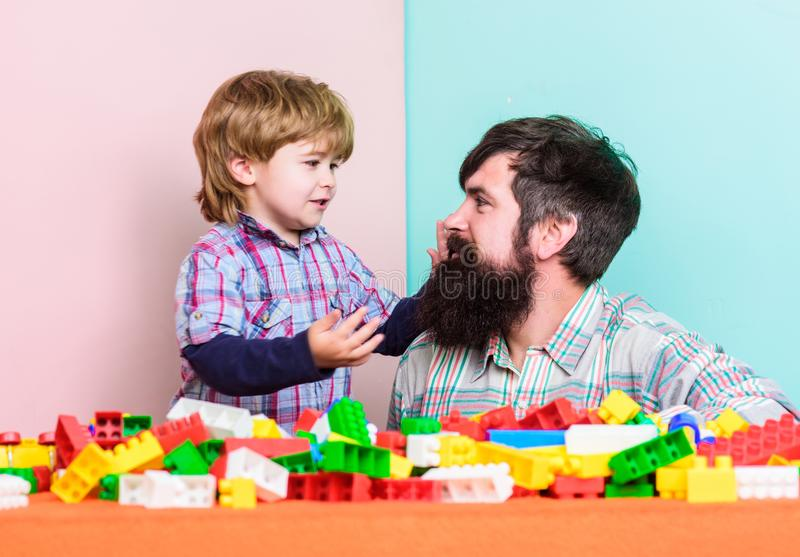 Every dad and son must do together. Dad and kid build plastic blocks. Child care development and upbringing. Father son stock photography