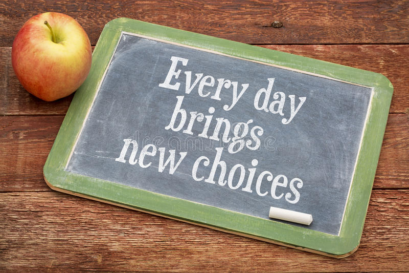 Every day brings new choices on blackboard. Every day brings new choices - motivational positive words on a slate blackboard against red barn wood stock image